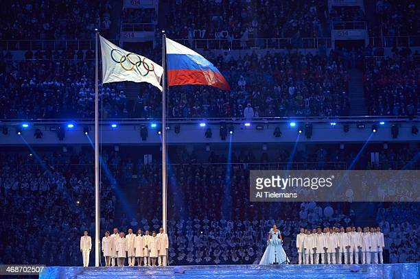 2014 Winter Olympics View of soprano singer Anna Netrebko performing with Russian athletes in background as Olympic flag rises during ceremonies at...