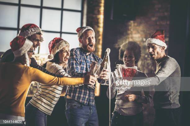 opening champagne on a christmas party in the office! - opening party stock photos and pictures