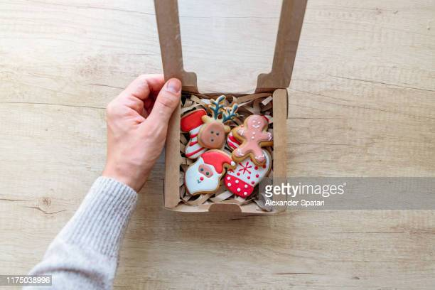 opening christmas present with christmas cookies, personal perspective view - public celebratory event stock pictures, royalty-free photos & images