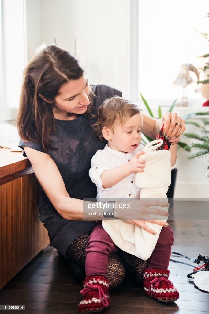 Opening gifts on Christmas morning for aunt and nephew. : Stock Photo