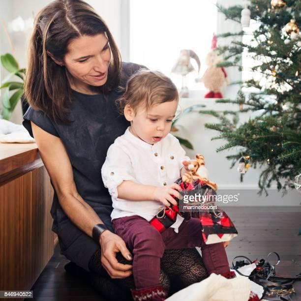 opening gifts on christmas morning for aunt and nephew. - zia e nipote foto e immagini stock