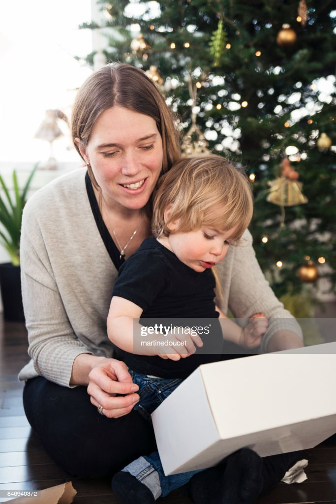 Opening gifts on Christmas morning for mother and son. : Stock Photo