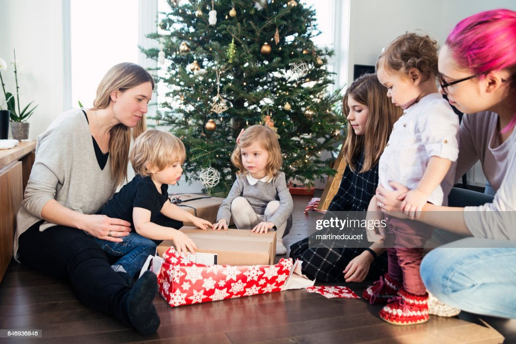 Opening gifts on Christmas morning for small family. : Stock Photo