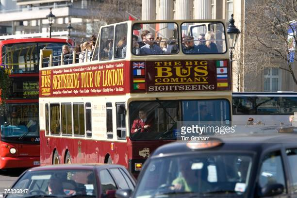 Opentopped sightseeing bus travelling in Trafalgar Square downtown London city centre England United Kingdom