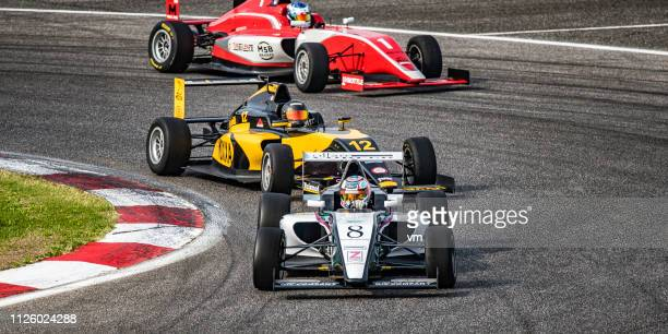 open-wheel race cars on a race track - grand prix motor racing stock pictures, royalty-free photos & images