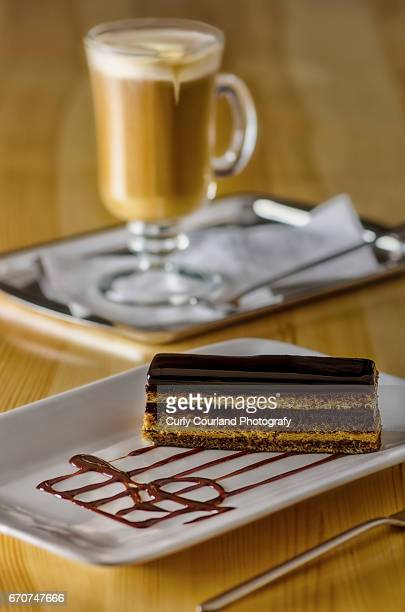 Opera cake served on the rectangular plate with chocolate stave and treble cleff and Irish coffee