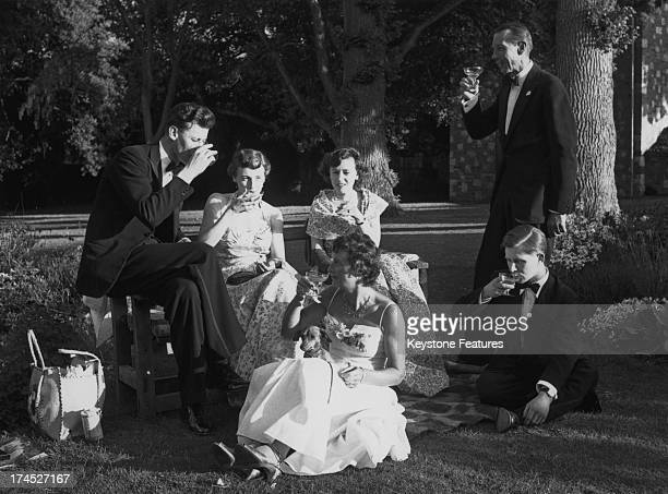 Opera goers enjoy the evening sunshine in the gardens of Glyndebourne during the interval of the 'The Marriage of Figaro' Sussex 1955