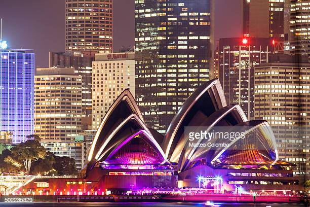 Opera house and skyline with buildings of the central business center CBD at night, illuminated with colorful lights.
