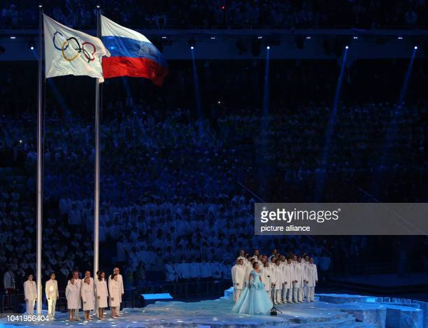Opera singer Anna Netrebko of Russia sings the Olympic anthem next to the Olympic flag and flag of Russia during the Opening Ceremony in Fisht...