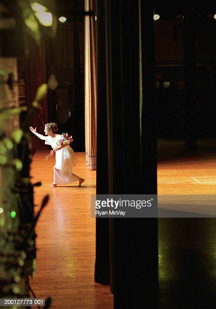 Opera singer holding bouquet of flowers, taking bow on stage