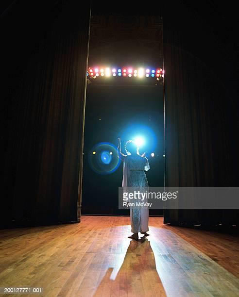 Opera singer performing on stage, reaching toward spotlight, rear view