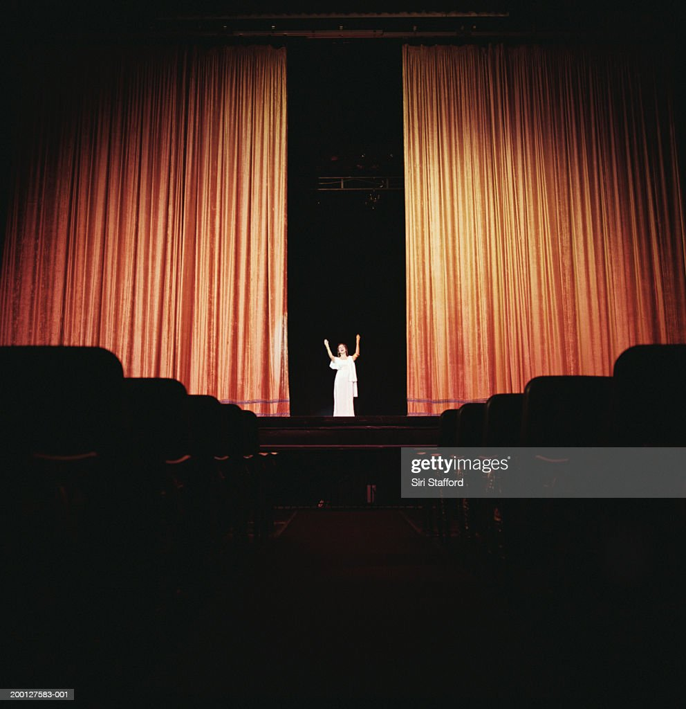 Opera singer standing between curtains on stage : Bildbanksbilder
