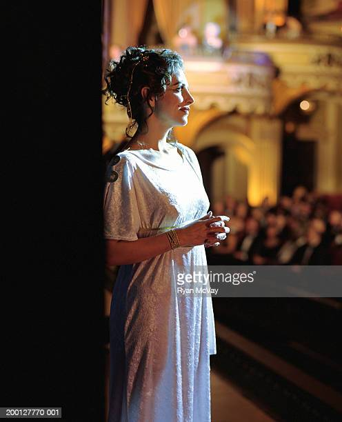 Opera singer standing on stage, looking outward, profile