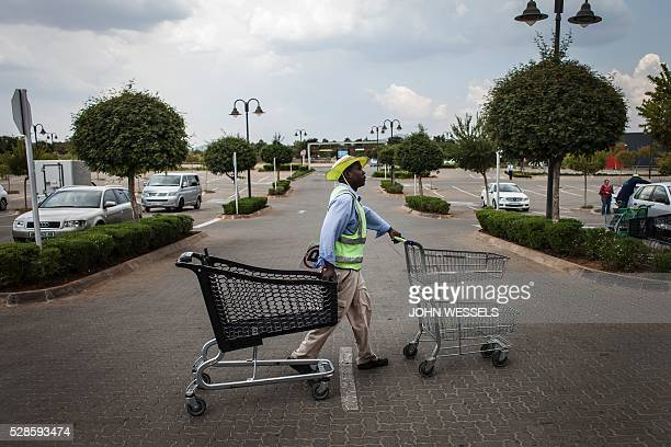 TOPSHOT Opera singer turned car guard Abdias Mkhabela clears trollies from his section of the parking lot on April 26 2016 in Hartbeespoort South...