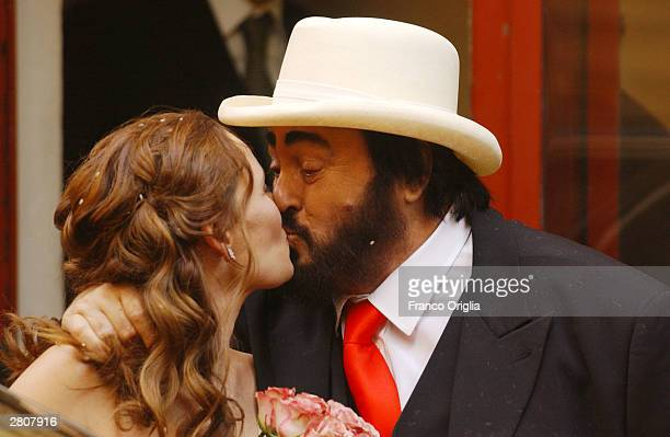 Opera star Luciano Pavarotti kisses Nicoletta Mantovani as they leave the Teatro Comunale at the end of their wedding December 13 2003 in Modena Italy