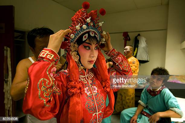 Opera star Zhang Lixuan gets ready backstage before a performance at the Peking Opera at the Regal Palace theater August 11 2008 in Beijing China...