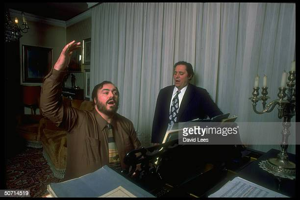 Opera tenor Luciano Pavarotti playing piano and singing while also accompanying father Fernando at home
