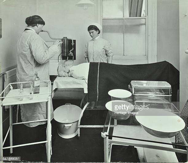 Operating Room Fulham School Treatment Centre London 1914 A female doctor and nurse attending to a patient Artist unknown