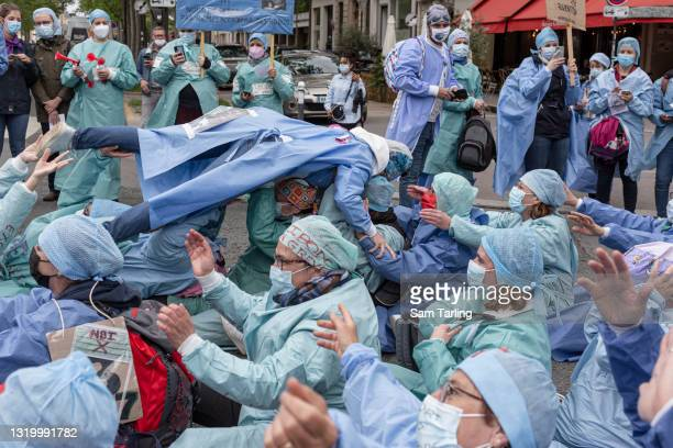 """Operating room nurse crowd-surfs during a strike to protest the """"contempt"""" shown to them in a overhaul of France's healthcare system, the """"Ségur de..."""