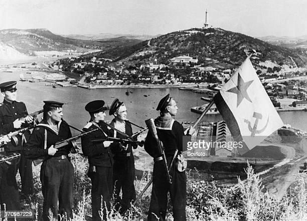 Operation august storm , a landing party of sailors of the soviet pacific fleet hoisting a flag over port arthur bay, manchuria, september 1945.