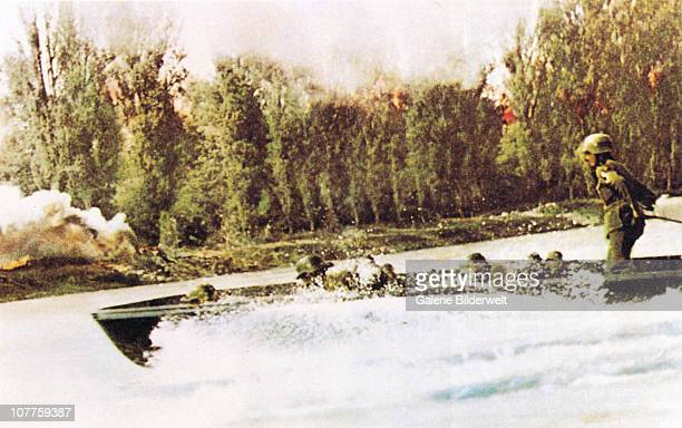 Operation Barbarossa German Wehrmacht soldiers are under fire going down the river in a boat 1941Trees near them have caught fire They are part of...