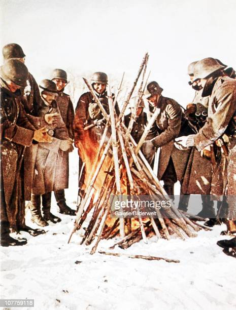 Operation Barbarossa Soldiers have been exposed to the cold and are warming up near a fire on the Eastern Front in Russia during the winter 1941 They...