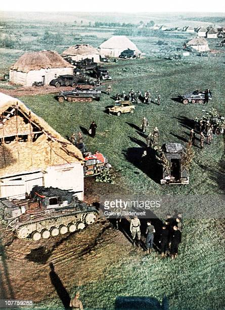 Operation Barbarossa Tanks and other vehicles have arrived in a small rural village on the Eastern front 1942 A Nazi flag has been placed near the...