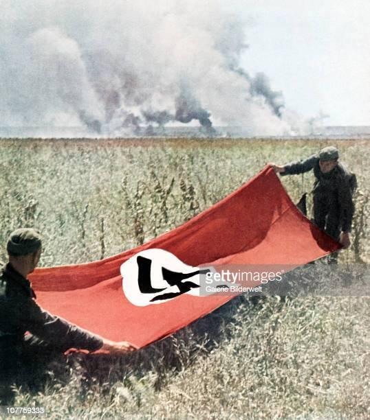 Operation Barbarossa Two Wehrmacht soldiers are holding a Swastika flag to protect against friendly fire 1942 Fighting is going on nearby on the...