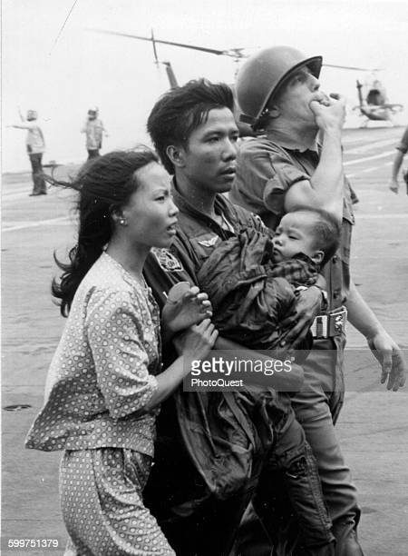 Operation Frequent Wind A South Vietnamese helicopter pilot and his family safely aboard the USS Hancock are escorted by a Marine Security Guard to...