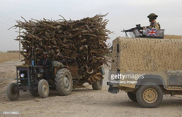 British Forces In Afghanistan 2006 - 2007, A local civilian driving a tractor loaded with wood passes an Army landrover during the first British Army...