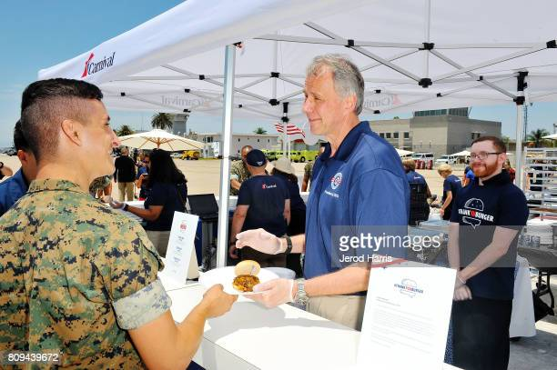 Operation Homefront CEO and President John Pray serves hamburgers to Marines at Carnival Cruise Line's First Ever Socially Powered BBQ at Marine...