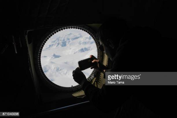 Operation IceBridge project scientist Nathan Kurtz photographs from NASA's research aircraft in the Antarctic Peninsula region on November 3 above...