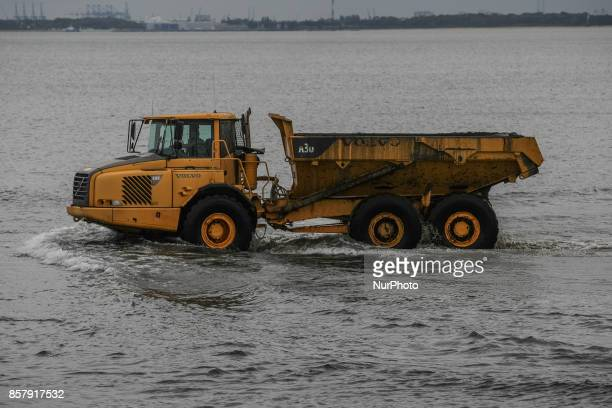 Operation of dredging of Gdansk Bay by the Sopot pier using Volvo heavy duty trucks and CAT backhoe loaders is seen in Sopot Poland on 5 October 2017...