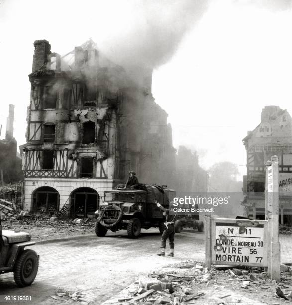 A Canadian MP controls the traffic on place Saint Gervais 17th August 1944 Buildings are in ruins and on fire A Chevrolet truck towing a Bofors...