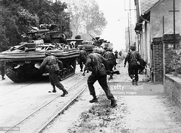 Operation Overlord DDay 6 June 1944 Sherman DD tanks of 'B' Squadron 13th/18th Royal Hussars support men of No 4 Army Commando on the Rue de Riva...