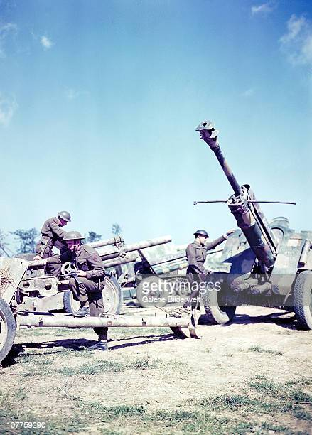 Operation Overlord Normandy, British soldiers inspect a German F-22 USV 75 mm gun and other weapons. July 1944. These guns have been captured by...