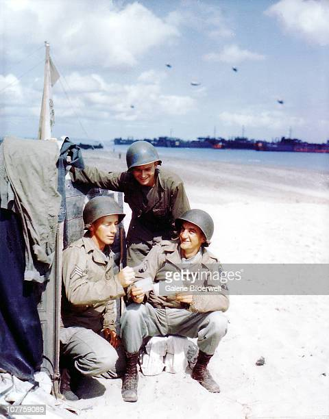Operation Overlord Normandy Three American soldiers from the 1st Engineer Special Brigade are looking at photos from home June 1944 Landing Ships...