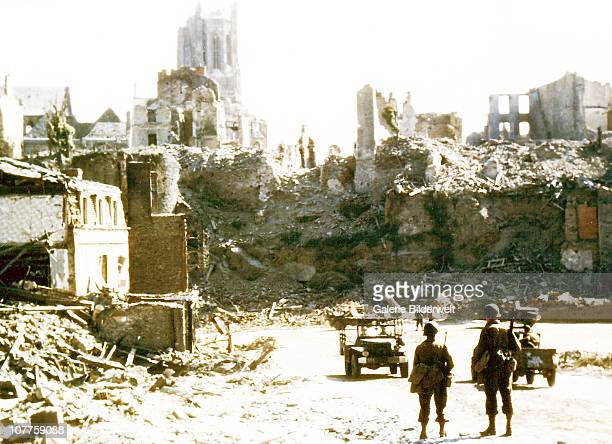 Operation Overlord Normandy Two American soldiers are watching two United States Army jeeps driving through the ruins of the center of SaintLo August...