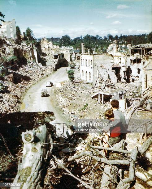 Operation Overlord Normandy Two children are watching an American Army jeep driving through the ruins of SaintLo August 1944 The town was almost...