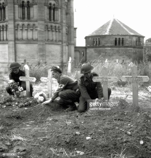 Three soldiers of the 23rd Field Ambulance of the 3rd Canadian Infantry Division place flowers on graves. June 1944. Two soldiers wear the armband...