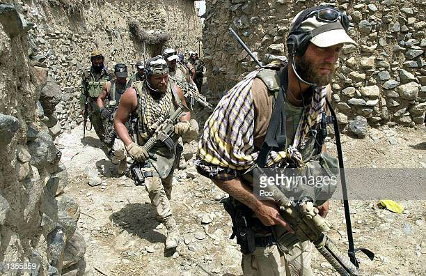 S ODA Operational Detatchment ATeam Special Forces Group walks through a village August 22 2002 in Narizah140 kms east of Kabul Afghanistan US...