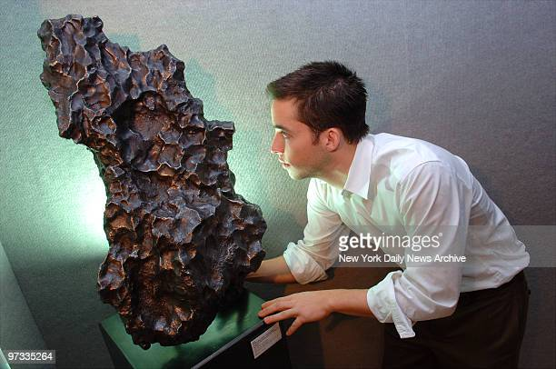 Operations Coordinator Adam Johnson inspects a meteorite on display at Bonhams on Madison Ave., which will soon be up for auction. Expected to fetch...