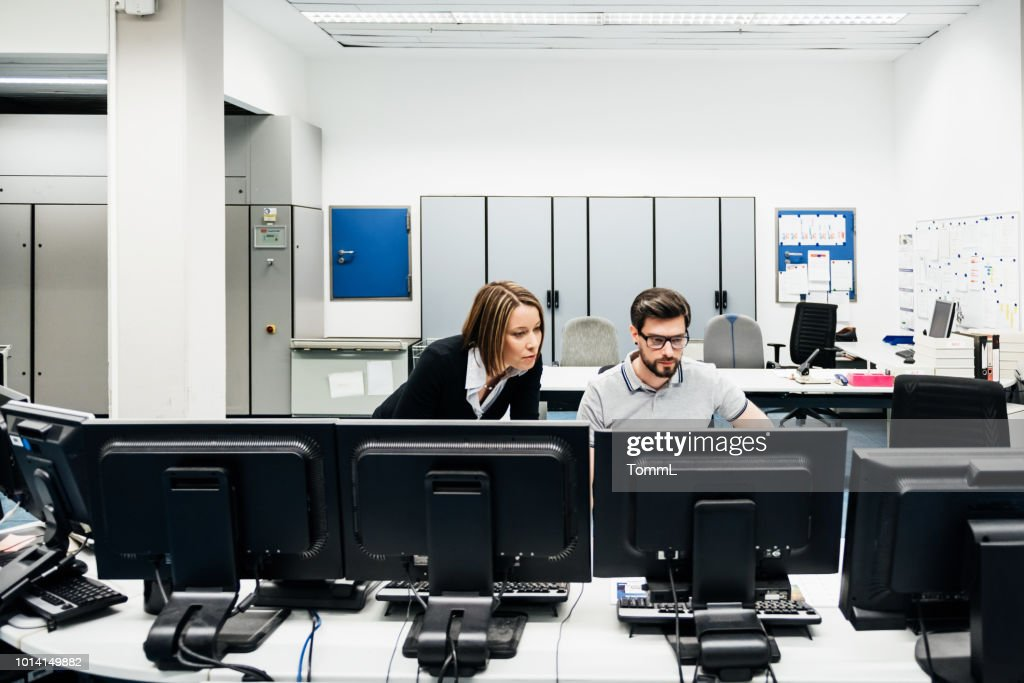 Operations Manager Assisting Colleague In Factory Control Room : Stock Photo