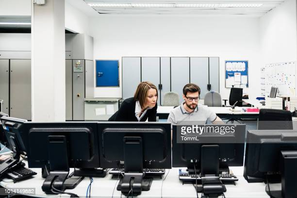 Operations Manager Assisting Colleague In Factory Control Room