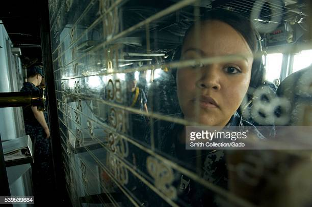 Operations Specialist Seaman Lorraine Cervantes writes on the status board in the pilothouse aboard the US 7th Fleet flagship USS Blue Ridge LCC 19...