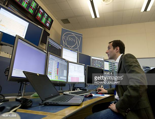 ROUX LHC operator Mirko Pojer watches screens on February 10 2015 at the CERN Control Center at the European Organisation for Nuclear Research in...