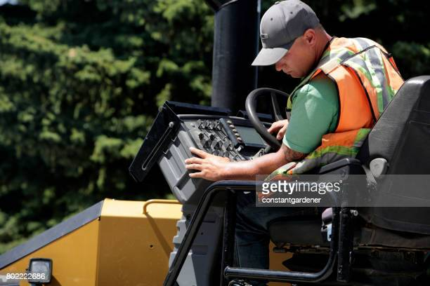 operator of asphalt paving equipment - asphalt paving stock photos and pictures