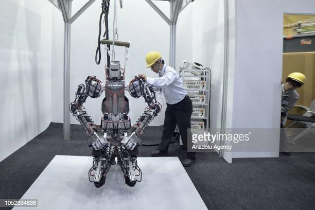 A operator of Kawasaki Heavy Industries Ltd's checks a Kawasaki Heavy Industries Ltd's Kaleido humanoid robot displayed at the Japan Robot Week 2018...