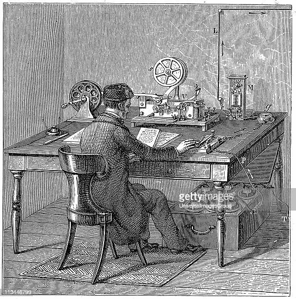 Operator sending a message on a Morse electric printing telegraph by tapping out code with key Under table are we cells supplying electricity Wood...