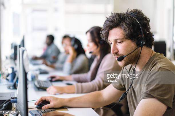 operator talking on headset while using computer - coworker stock pictures, royalty-free photos & images